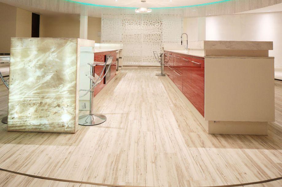 CASACOR Paraná - Cozinha Show. O arquiteto Gastão Lima criou um ambiente ideal para receber eventos, com uma ilha de trabalho ao centro e um piso que traz o calor da textura amadeirada. Os acabamentos dos móveis em alto brilho criam um resultado elegante. A iluminação azul em LED e as cortinas de alumínio finalizam e emolduram o espaço.