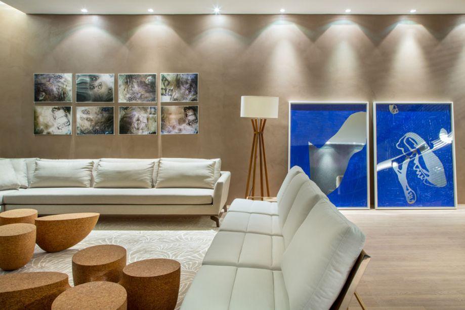 """Chocolate com Café - Para criar um ambiente com cara de casa, Leonardo Pascual escolheu um sofazão (3,30m x 3,20m) em L, forrado com linho castanho, e uma paleta de cores aconchegante, variando entre o bege e o marrom. Uma das paredes foi revestida com tecnocimento na cor cacau, em sintonia com o piso flutuante (Ekko) de madeira. As mesinhas de centro e de apoio são de Jader Almeida para a Finish. A iluminação de Fernanda Vasconcellos foi feita com placas teladas forradas com linho presas ao teto – a luz fica atrás das telas. """"O resto da iluminação é indireta, lavando as paredes"""", conta o arquiteto, que ainda escolheu fotos de sua mãe, Laura Bonfá Burnier, para finalizar."""