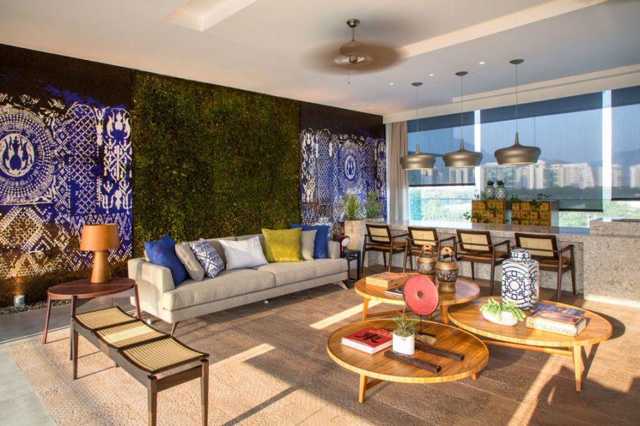 Varanda Lounge Bar - O espaço de Rodrigo Barbosa, com 72m², é aberto para os dois lados e traz um conceito de lounge, com confortáveis sofás, poltronas, banquetas, mesinhas baixas (em parceria com a marca Franccino Giardini), almofadas e cortinas cheias de texturas (da Guilha). O piso em placas de porcelanato granito (Lipica Gray da Revix) se confunde com o tapete central em réguas de porcelanato, que remetem à madeira de demolição (Tanto Revestimentos). A bancada do bar, com 6m de comprimento, é finalizada com silestone e fitas de LED. Um toque asiático vem nos dois painéis laterais, remetendo a uma grade em tons de roxo, preto, cobre, com papel de parede franceês que mimetiza pastilhas bizantinas, ambos da Guilha. Os jardins verticais foram desenvolvidos pelo paisagista Paco Alvarez, do Studio dagema. Repare também no teto: os ventiladores com pás em palha natural, vieram da Amazônia.