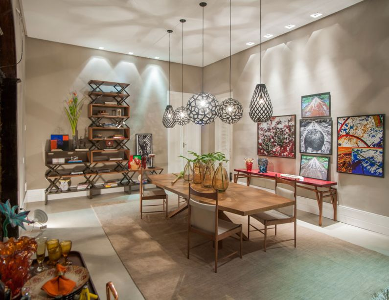CASACOR Alagoas - Sala de Jantar - Valéria Cox apostou no design brasileiro e elege a madeira como matéria-prima em destaque, sempre com linhas delicadas. A estante é composta de prateleiras e nichos organizados de forma casual, em uma proposta também seguida no mix de luminárias e telas.