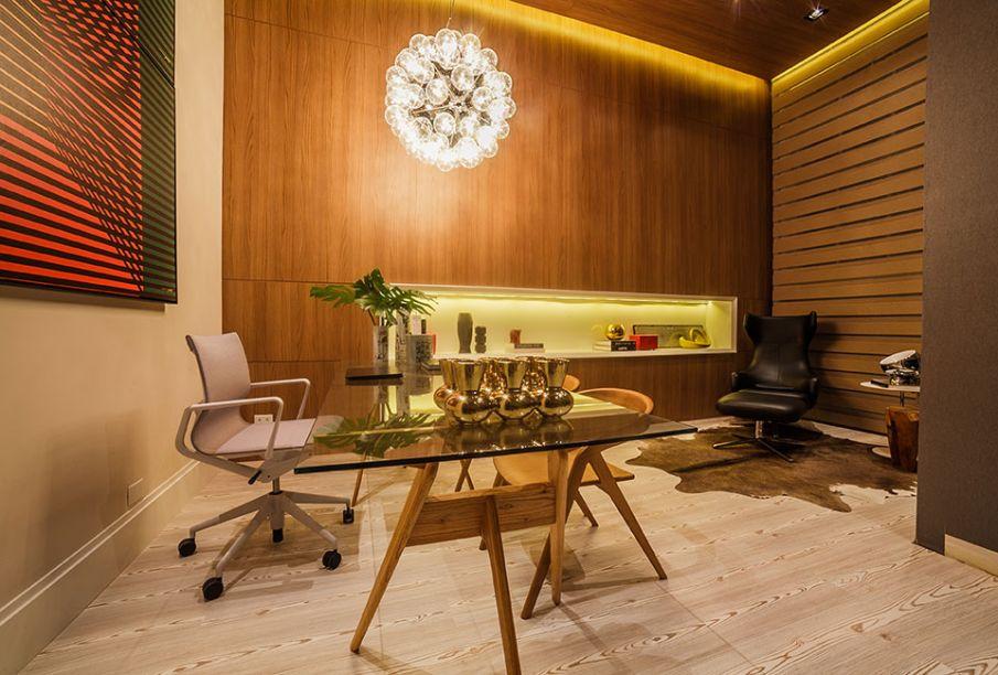 Home Office - Carla Grüdtner. No espaço de 21 m², a madeira é destaque. O piso laminado em pinus e o revestimento de melanina no teto e nas paredes criam uma caixa aconchegante, recortada por um nicho embutido com pintura laca. Na iluminação, a escolha foi o LED, mais ecológico.