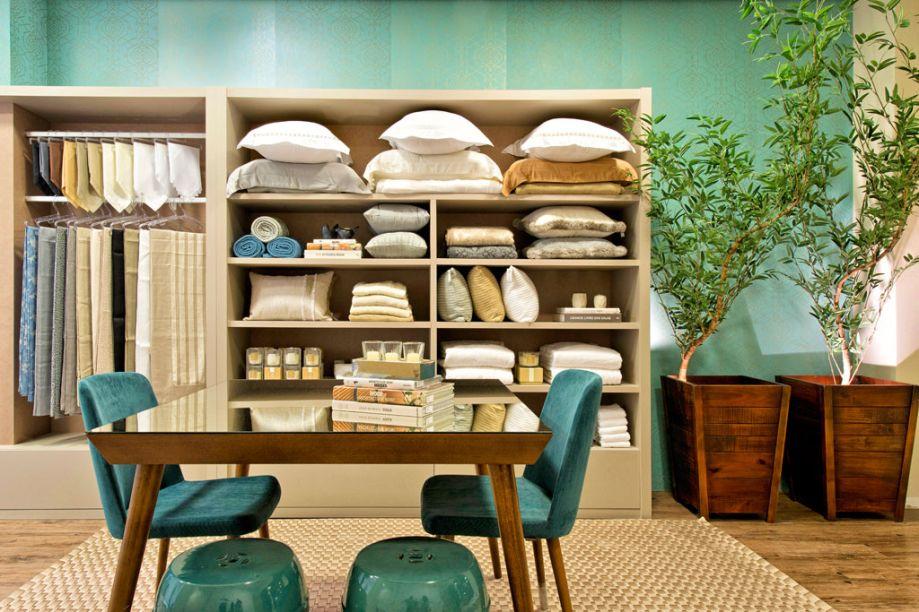 A Loja da Casa. O projeto da arquiteta Manu Cancela converteu os 40m² disponíveis em uma loja de produtos para cama, mesa e banho. O mobiliário neutro apresenta as peças, deixando as cores marcantes para o papel de parede. O tapete em seda dourada foi produzido especialmente para o espaço.
