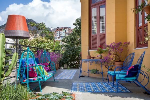Jardim da Frida Kahlo - Paula Bergamin. Para deixar o ambiente mais alegre, Paula optou por tons fortes de azul, amarelo, rosa e turquesa. Itens de antiquário e outros contemporâneos contracenam com elementos usados e reciclados, como móveis de ferro, objetos antigos e tecidos garimpados no México. Repare também no piso pintado.