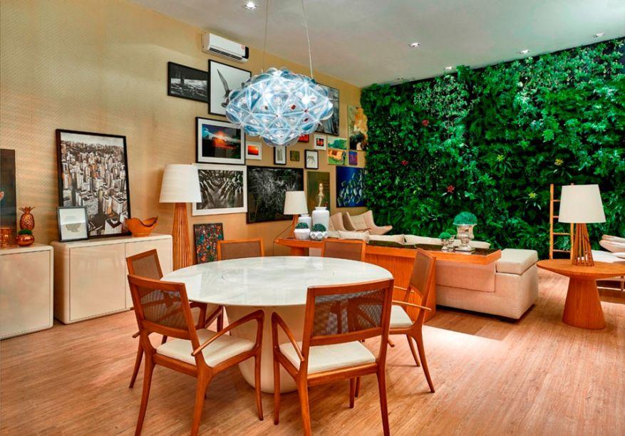 CASACOR Brasília Loft Lake. Miguel Gustavo apresenta um espaço acolhedor com muita madeira e a presença marcante da parede verde. Ele soltou vários móveis das paredes para gerar mais espaços de exibição de telas de arte e fotografias.