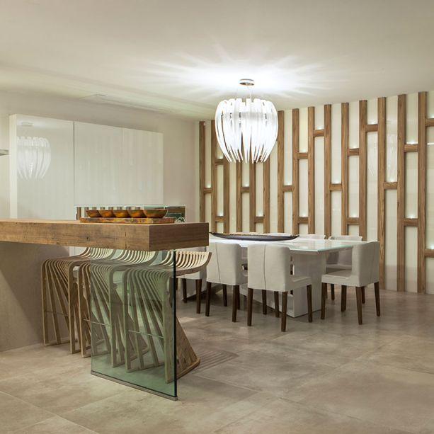 CASACOR Espírito Santo - Flat urbano. Letícia Finamore adotou o vidro branco nos detalhes e no mobiliário, sugerindo leveza em cada canto do ambiente. A estrutura em madeira redesenha a parede principal da sala de jantar.