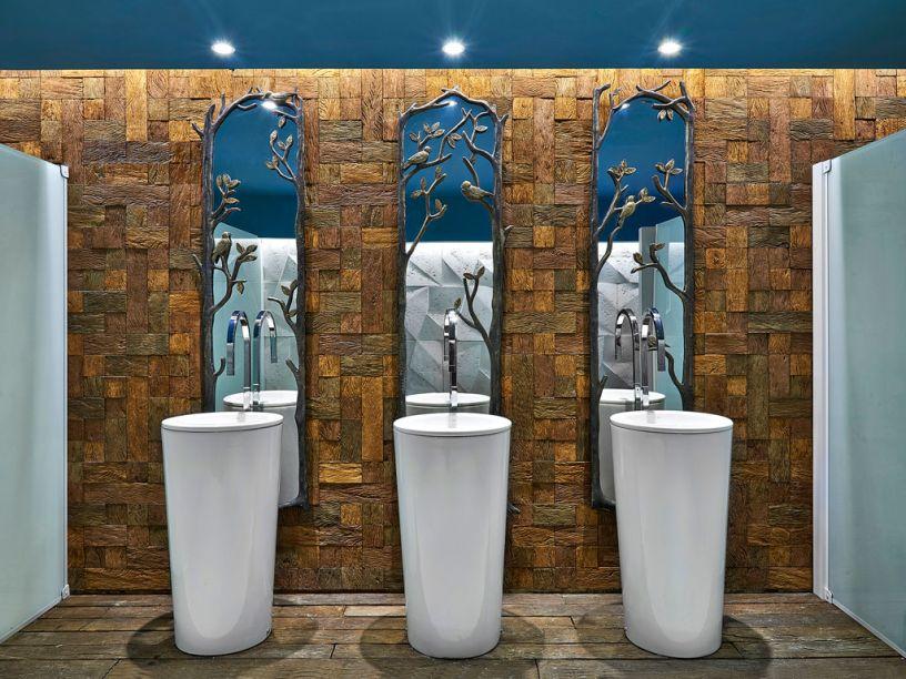 Banhos Públicos - Priscilla Barros Pettersen e Priscilla Sotério Nunes rebaixaram o gesso e utilizaram a cor azul Tiffany, além de pontos de luz. Sobre a parede coberta de placas de madeira, os espelhos com molduras inspiradas em galhos de árvores refletem o revestimento 3D utilizado na parede oposta. As cubas dispensam o uso da bancada e, assim, ganha-se mais leveza e espaço.