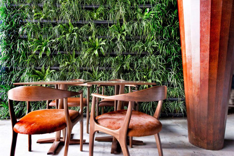 Resto Garden. O arquiteto paisagista Wolfgang Schlögel elabora um espaço para convivência e pequenas refeições em um jardim interno, integrado com outros ambientes graças a panos de vidro. O mobiliário em madeira foi revestido com pele natural, acompanhado de grandes vasos em aço Corten que simulam árvores. O jardim vertical deixa o resultado mais envolvente.
