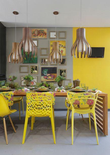 Varanda Gourmet - Arielle Nogueira, Marcos Kaian, Oderito Freitas e Luciana Tenuta. A aposta é na brasilidade e na descontração. A energia do amarelo conecta visualmente as cadeiras diferentes, os quadros e o tecido de chita sobre a mesa.