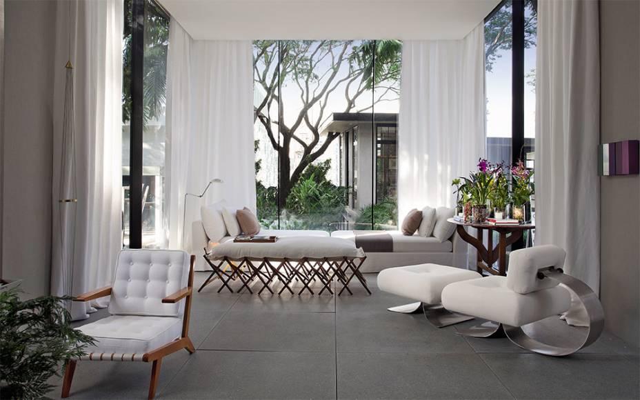 A Poltrona e a Banqueta Alta (direita) de Oscar Niemeyer são os destaques do<span>estar que possuía clima de biblioteca. As peças formavam o conjunto perfeito para quem quisesse ler um livro ou apreciar a vista do jardim de inverno,uma extensão natural do espaço, que se transforma em uma caixa de vidro que avança na paisagem. CASACOR São Paulo 2016.Living e Jardim de Inverno - Dado Castello Branco.</span>