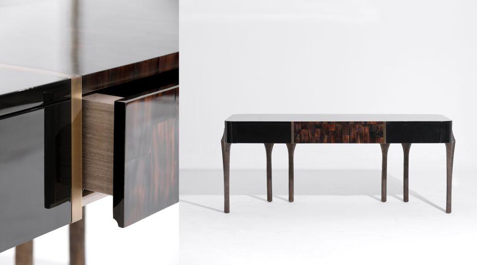 OSCAR –Uma escrivaninha sofisticada de laca preta, com painel central revestido em chifre e emoldurado emlatão. A superfície é apoiada por seis pernas de bronze moldado, esculpidas, com acabamento empatina 'hena' escura. Esse elemento é a única referencia literal a Niemeyer – as colunas do Palácio daAlvorada.A escrivaninha combina perfeitamente o passado e o presente, tradição a uma estética contemporânea.Com dimensões generosas, a Oscar é composta de nuances contrastantes; a sua superfície altamentepolida da laca contrasta intencionalmente com a aparência rústica das pernas moldadas em bronze. Àelegância sóbria da laca preta, inserimos um painel de chifre natural, emoldurado por uma guarnição delatão antigo.