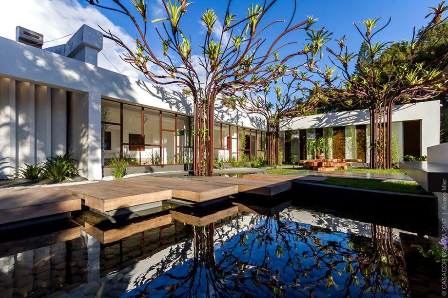 """TEA GARDEN - CARLA BLANCO, JOSELYNE ADAD E LUIS EDUARDO AÑEZ. Os princípios de Kazuo Shinohara e o Jardim Botânico de Cingapura orientam o projeto, com suas três estruturas metálicas chamadas """"Árvores de Bromélias"""". O lago é percorrido sobre placas em madeira, ressaltando o contato com a natureza para favorecer o relaxamento e a meditação."""