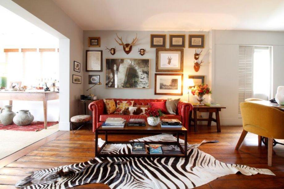 Nas paredes, quadros e esculturas de animais, conferem a esta sala um clima de chalé inglês. Ao centro, o sofá Chesterfield empresta cor ao lugar.