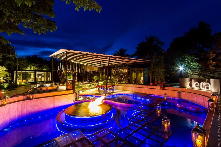 CASACOR Bolívia. Pool Bar Deca - Alejandra Iriarte. A dualidade do fogo em relação a elementos como água e ar inspira o espaço, setorizado em quatro piscinas conectadas, bar e lounge. As luzes acompanham o ritmo da música.