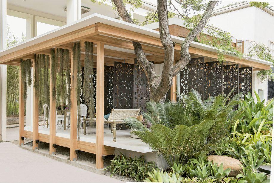 Mariana Crego - Casa Sustentável. As construções de madeira da Tailândia inspiram o projeto, erguido com um método que simplifica montagem e desmontagem. A sustentabilidade é valorizada em painéis fotovoltaicos que captam luz solar e geram energia, no reúso de água da chuva e no revestimento na cozinha, que reaproveita lâmpadas fluorescentes.