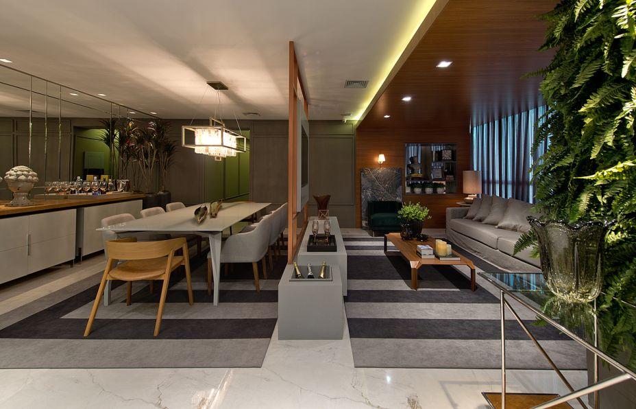 Living Salon Gris - Caroline Oenning e Luiz Gustavo Schmidt. Cozinha e sala de jantar são integrados, mas contam com sutil separação da sala de estar, com painel de estrutura metálica acobreada. Ele é apoiado no aparador em corian e laca, que inclui uma champanheira. Acabamentos com brilho e texturas rústicas se intercalam, mas os materiais naturais predominam, como a madeira do pórtico que abraça o sofá.