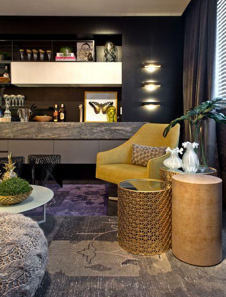 Mrs. Me - The Pub For Women - Herbert Evaristo e Luiza Fortkamp. Os bares e hotéis de Dubai, com pitadas luxuosas de roxo, amarelo cítrico e ouro, são a inspiração do ambiente para mulheres poderosas. Tapetes sobrepostos e o pufe em crochê definem a atmosfera de lounge. As texturas são tão sofisticadas quanto as cores, como o couro e o dourado nas mesas de apoio.