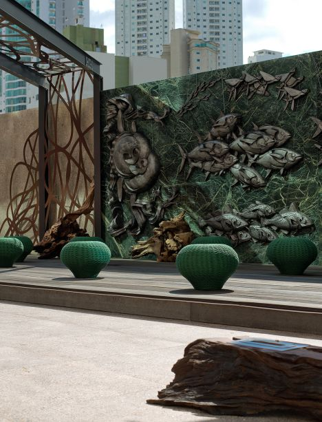 """<span style=""""font-weight: 400"""">Praça CASACOR - Juliana Loffi e Rodolpho Guttierrez. Neste ambiente de slow design, para ser apreciado sem pressa, citações às belezas do litoral catarinense. A estrutura metálica foi criada com exclusividade, assim como os móveis em madeira de reaproveitamento, com raiz exposta. As esculturas de peixes são sobrepostas ao painel em mármore.</span>"""