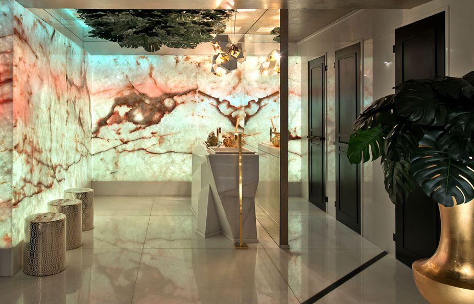Lavabos Funcionais - Elaine Gurevich e Evandro Cruz. A beleza natural do mármore translúcido com iluminação embutida se impõe no ambiente de 35 m². O material também está na bancada lapidada, com cubas encaixadas e metais dourados para complementar. Além da sofisticação, as superfícies lisas facilitam a limpeza. Outro ponto alto, literalmente, é o teto com folhas de Costela de Adão.