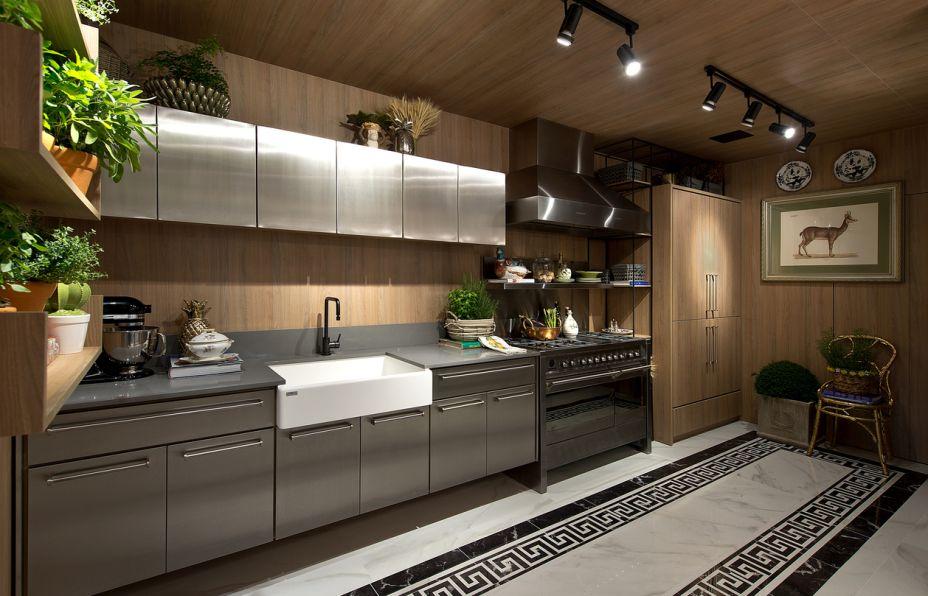 Apartamento de Solteiro com Galeria Gourmet - Fernando Dal Bosco e Mariana Ribeiro. A cozinha é protagonista, com um ar industrial e todas as funcionalidades: um belo fogão, dois fornos, geladeira embutida e o inox sempre bem-vindo. Para um resultado acolhedor, folhagens e hortaliças.