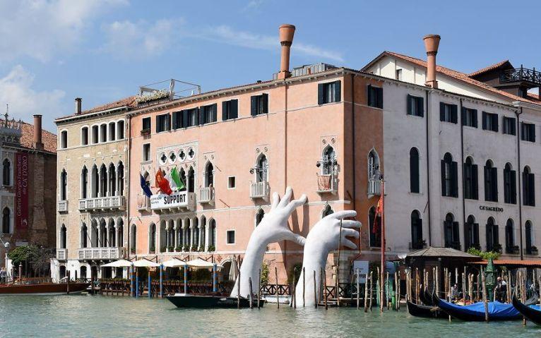 As mãos de Lorenzo Quinn O artista italiano Lorenzo Quinn construiu uma escultura monumental para a Bienal de Arte de Veneza 2017 para chamar a atenção para o aquecimento global