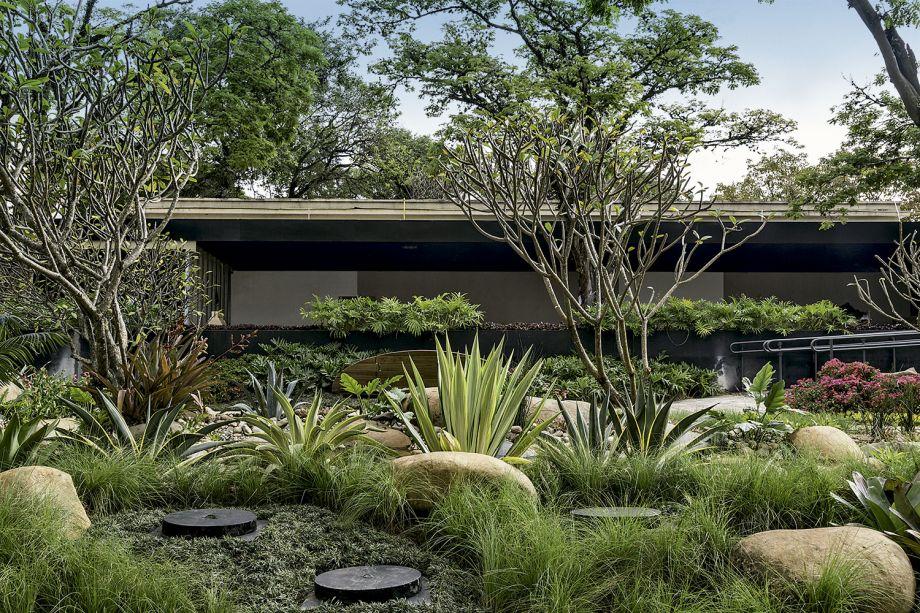 Ricardo Pessuto - Praça Urbana CASACOR. Com 535 m², tem a dimensão de um parque e permitiu criar um lago de 100 m², rodeado por pedras monumentais. A coleção de bancos desenvolvida pelo profissional é apresentada em meio às plantas tropicais e nativas, como jasmim-manga, aspargos, bromélias, russélias, bambu-negro, estrelítzias.