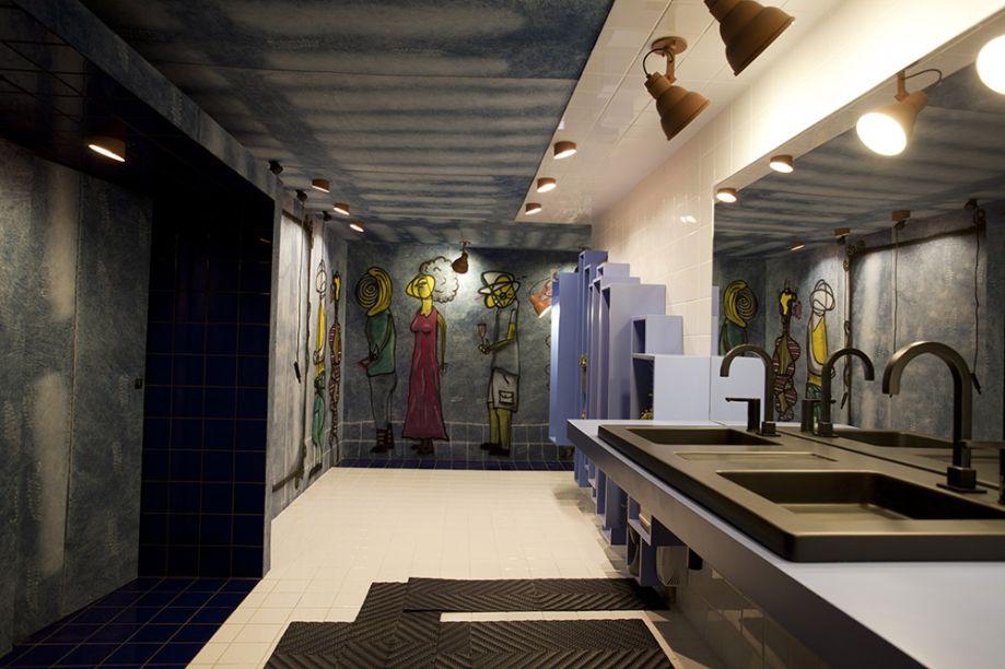 Zina Arquitetura - WC Unissex. O ambiente é neutro, com paredes revestidas em jeans - o tecido mais democrático de todos. Os grafites confirmam o espaço receptivo à diversidade.