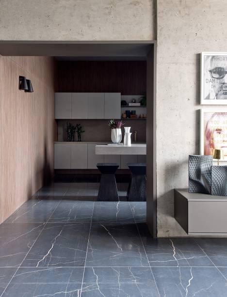 CASACOR Balneário Camboriú. A Sala de Concreto - Salvio Moraes Jr. e Moacir Schmitt Jr. o piso em mármore se contrasta com a madeira das paredes e a marcenaria.