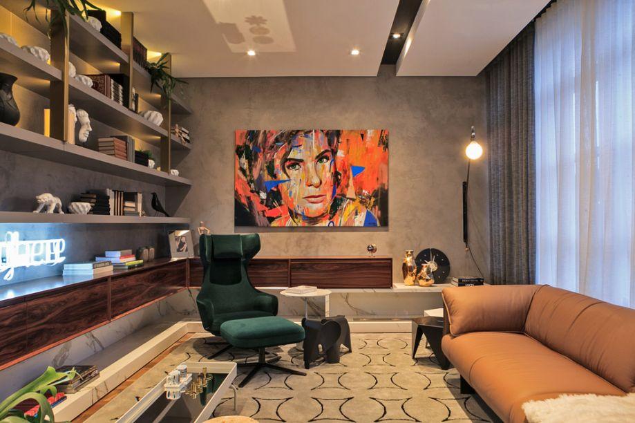 Biblioteca - Carla Grüdtner. A poltrona em veludo verde e o sofá em couro natural garantem a tranquilidade da leitura no ambiente de 22m². Na parede, a textura à base de água vem no mesmo tom da estante, que traz detalhes em aço dourado. O aparador em lâminas de Nogueira abraça o espaço.