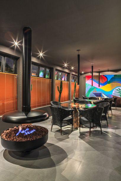 Restô Garden Compagas - Wolfgang Schlögel. Com 150m² à disposição, o paisagista escolheu ampliar ainda mais o espaço ao posicionar as mesas junto às grandes janelas. A sensação é de estar em uma varanda, com o conforto de mesas e cadeiras produzidas à mão. Mas o principal elemento, sem dúvida, é a generosa lareira à gás.