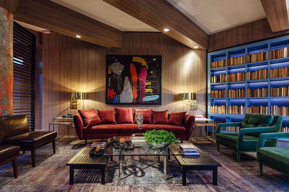 Superloft - Luiz Sentinger. A estante em laca acetinada azul possui detalhes de iluminação em LED. Ela divide a atenção com o sofá curvo na cor bordô e as poltronas verdes. A madeira clara abraça paredes e vigas, para acentuar a sensação de conforto.