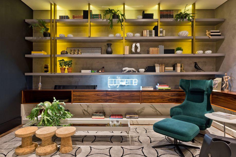 <span>Biblioteca - Carla Grüdtner. A poltrona em veludo verde e o sofá em couro natural garantem a tranquilidade da leitura no ambiente de 22m². Na parede, a textura à base de água vem no mesmo tom da estante, que traz detalhes em aço dourado. O aparador em lâminas de Nogueira abraça o espaço.</span>
