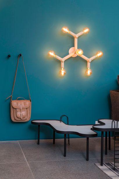 Para além de estampas e paredes, a geometria também reina no formato de móveis e peças de decoração, como aqui no espaço da Todos Arquitetura, onde até a luminária segue o estilo.