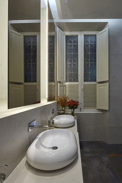 Banheiros Públicos - B&L Arquitetura. Du Leal e Eduardo Beggiato apostaram no piso em porcelanato metalizado Corten e em paredes no mesmo material, na tonalidade dune. Espelhos magrinhos sobem até o teto e se destacam com iluminação de fundo.
