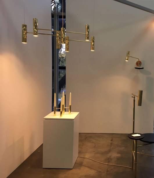 """<strong>Ana Neute</strong> - As incríveis peças da designer, que também esteve com algumas delas na <a href=""""http://casacor.abril.com.br/mostras/sao-paulo/"""">CASACOR SP</a>, expõe uma nova coleção na MADE, de objetos dourados e sofisticados, com design arrojado e inovador. A profissional leva uma linha c<span>omposta por quatro peças em latão polido: a Coleção Elo, que apresenta castiçal, pendente, arandela e luminária de piso com mesinha.</span>Dentre os lançamentos, está a luminária Elo, que também assume a função de mesa para apoiar objetos."""