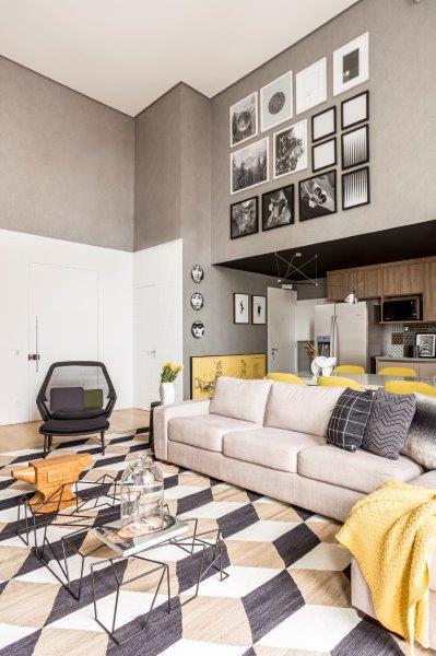 Na sala, o pé-direito duplo impõe suntuosidade ao projeto, ao mesmo tempo que valoriza o mobiliário.