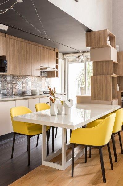 As cadeiras amarelas da cozinha chamam atenção a primeira vista e compõem com o tom ameno da marcenaria.