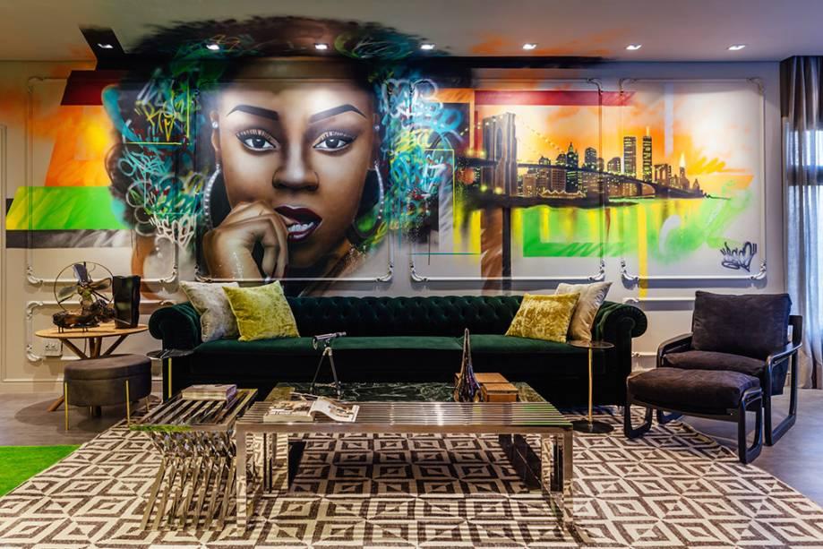 Street Loft - Sandro Jasnievez: neste espaço, o modelo de sofá verde escuro imprime elegância e um certo ar clássico, que contrasta com o mural de grafite, ao fundo.