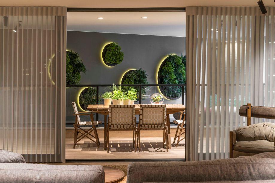 Gran Living - Walléria Teixeira. Na varanda, os jardins suspensos têm formato de mandala (Encanto Verde Paisagismo) e parecem se destacar da parede, graças ao efeito de iluminação com fitas de LED.