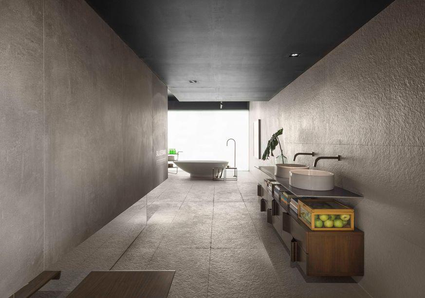 Sala de Banho - Priscila Gabriel. O minimalismo é bem representado no ambiente de 78m² e o cimento é um dos poucos materiais utilizados. Repare ainda na bancada slim, que apoia as cubas e é complementada pelo móvel em madeira. Tudo valoriza a experiência do banho de forma sensorial e natural.