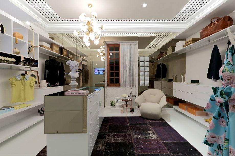 Closet com Sala de Estar - Sonia Beltrão, Gabriel Beltrão e Kátia Carapeba. A elegância discreta do branco define o espaço. Esse ambiente minimalista usa papeis de parede e um tapete iraniano envelhecido para completar sua proposta de forma equilibrada.