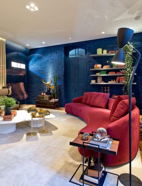 <span>Gourmet Living - Gabriel Bordin. O espaço enaltece o convívio e a integração em 52 m². Algumas paredes foram descascadas para revelar os tijolos e pintadas com o tom <strong>Azul Petróleo</strong>. O sofá curvo avermelhado atrai os olhares como um ponto de contraste da paleta de cores.</span>