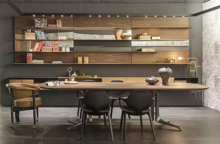 <span>2016 - <strong>Lounge</strong>. A sala de jantar integrada se estende a encontros de negócios. A estante de linhas elegantes ganha leveza ao intercalar a madeira com faixas de espelhos. A mesa Legg e as quatro cadeiras Clad são de Jader Almeida. Já a cadeira Beg, estofada em couro caramelo, é de autoria de Sérgio Rodrigues.</span>