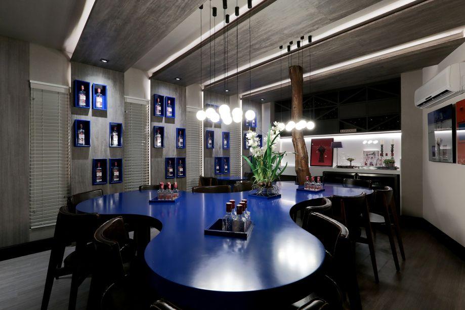 Wine & Gin Bar - Diego Ferraz. Uma grande mesa azul de linhas orgânicas envolvendo uma árvore central. O objetivo é criar um espaço elegante, porém despojado, ideal para conviver e confraternizar.