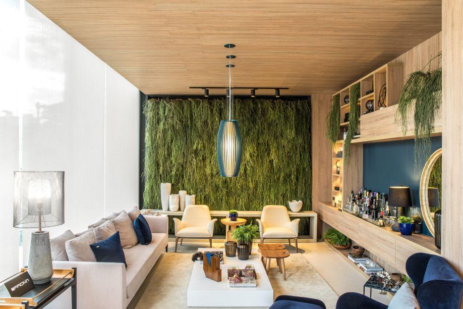 <span>Espaço Ambiente Ideal - Marília Bezerra. O espaço apresenta soluções construtivas de uma empresa. É fluido como em um loft, com o piso em Dekton garantindo a integração visual. O pé direito é elevado, e uma das paredes foi aproveitada para fazer um jardim vertical. No teto, a madeira garante o conforto acústico.</span>