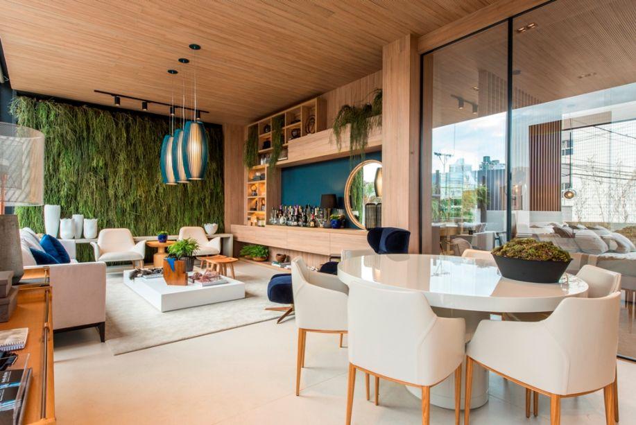 Espaço Ambiente Ideal - Marília Bezerra. O espaço apresenta soluções construtivas de uma empresa. É fluido como em um loft, com o piso em Dekton garantindo a integração visual. O pé direito é elevado, e uma das paredes foi aproveitada para fazer um jardim vertical. No teto, a madeira garante o conforto acústico.