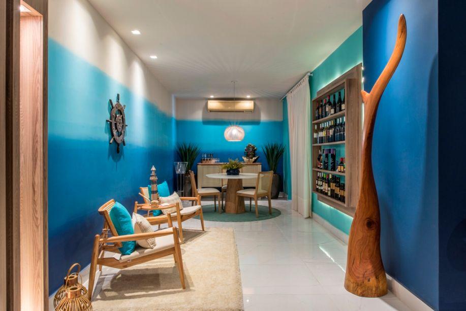 <span>Living e Lavabo - Lorena Azevedo. A pintura em degradê nas paredes traz as cores do mar para a ambientação. Móveis em madeira clara e tecidos crus compõem o clima praiano, além de outros elementos náuticos.</span>