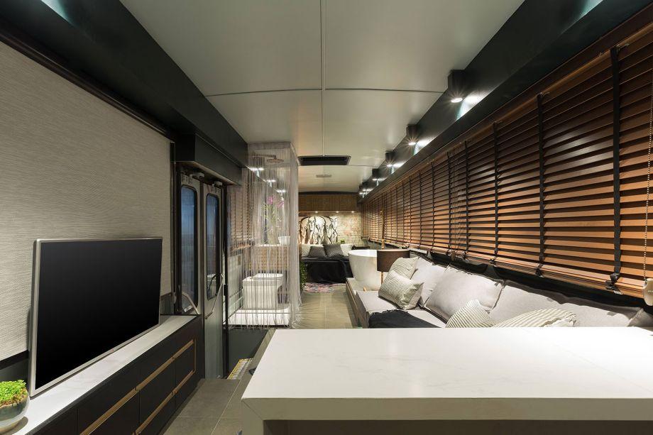 <strong>Loft Itinerante</strong> - Caio Prates. O loft que abriga<span>sala de estar e TV integrada, quarto, cozinha e banheiroem 2,38 m de largura e 10 m de comprimento é praticamente todo revestido compersianas em madeira e em alguns espaços, como no box do banheiro, possui cortinas em linho. O projeto foi pautado na versatilidade e montado dentro de um ônibus.</span>
