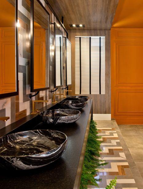 <span>Lavabo #Chevron - Carol Porto e Isadora Maestri. A composição de porcelanatos mescla texturas de mármore, cimento e madeira, em acabamentos fosco e brilhante. As peças foram cortadas uma a uma, com a montagem realizada na obra. As torneiras em dourado fosco acentuam o luxo das cubas marmorizadas, da Deca. Nos espelhos, o reflexo das boiseries conferem um toque clássico ao projeto.</span>