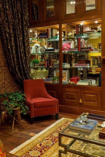 CASACOR Paraguay Biblioteca - Maria del Rosario Acosta e Isabela Acosta Bartels. O peso e a sobriedade dos tecidos, da tapeçaria e da madeira são suavizados pelas prateleiras em vidro, com fundo em espelho e iluminação. O vidro também confere leveza à mesa de centro, trabalhada em linhas retas.