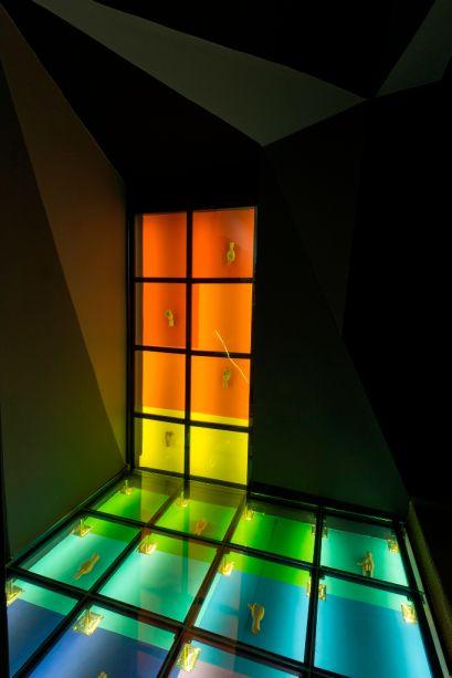 La escalera Suvinil - Laura Cass Goggin. Neste exercício conceitual, o gradiente de cores explora a versatilidade das tintas da marca. Tudo fica visível com piso e a parede em vidro, com iluminação. Paredes foram neutralizadas com tons escuros, e o resultado ganha ares de galeria.
